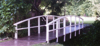 Bridge 1 - 20ft (6.10m) Hybrid style with flat beams and curved handrails. Posts and handrails painted white, boards stained Dark Oak. This garden bridge had a central beam to allow a ride-on mower. POA